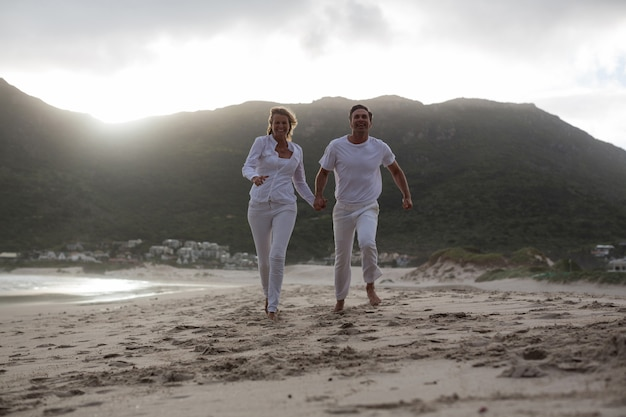 Casal maturo correndo na praia