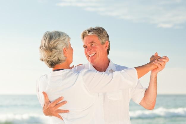 Casal maturo dançando na praia