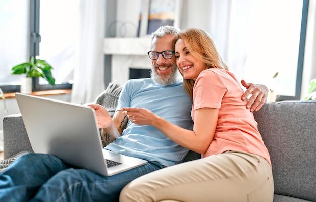 Casal maturo está sentado no sofá em casa com um laptop