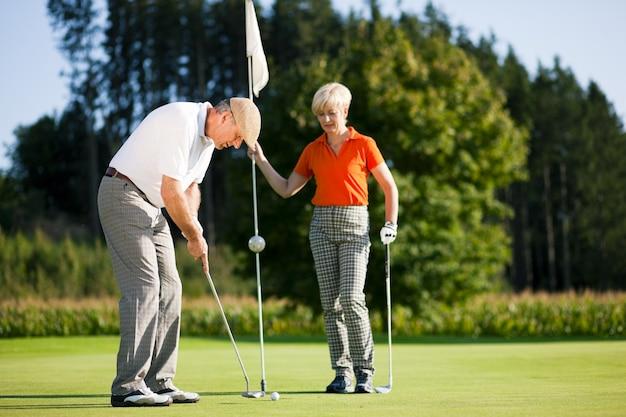 Casal maturo jogando golfe