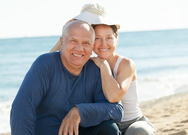 Casal maturo na praia do mar