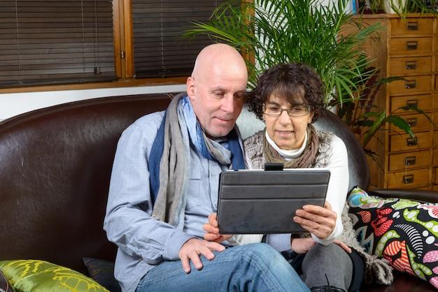 Casal maturo, olhando para um tablet digital