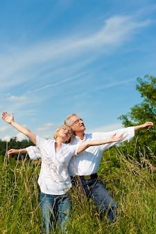 Casal maturo se divertindo em um campo ensolarado