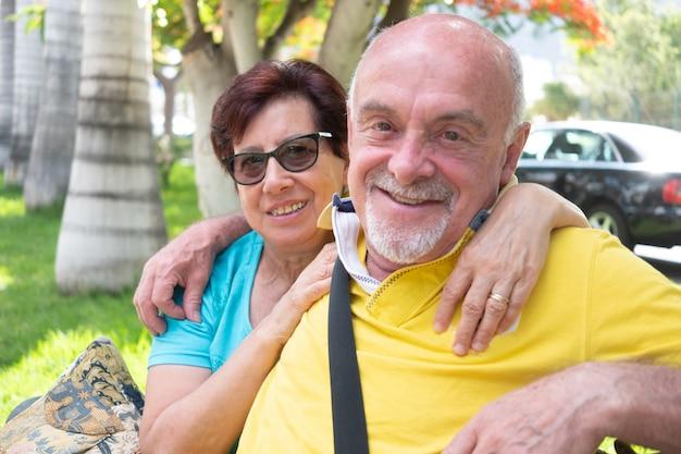 Casal maturo sentado ao ar livre em um parque público, sorrindo e olhando para a câmera Foto Premium