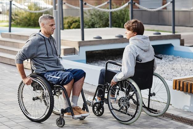 Casal maturo sentado em cadeiras de rodas, frente a frente, conversando enquanto toma ar fresco