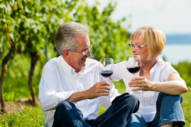 Casal maturo sentado na natureza tilintar de copos de vinho