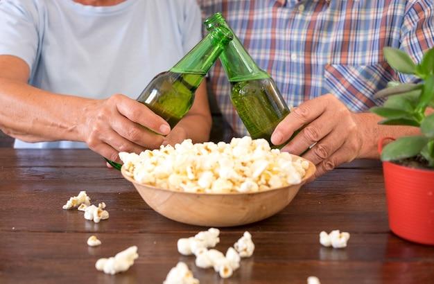 Casal maturo sentado no bar brindando com duas garrafas de cerveja e um pouco de pipoca. mesa de madeira
