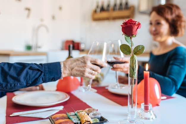 Casal maturo, tendo um jantar romântico em casa no dia dos namorados e fazendo torradas com vinho tinto
