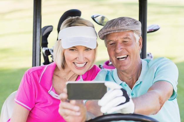 Casal maturo tomando selfie enquanto está sentado no carrinho de golfe