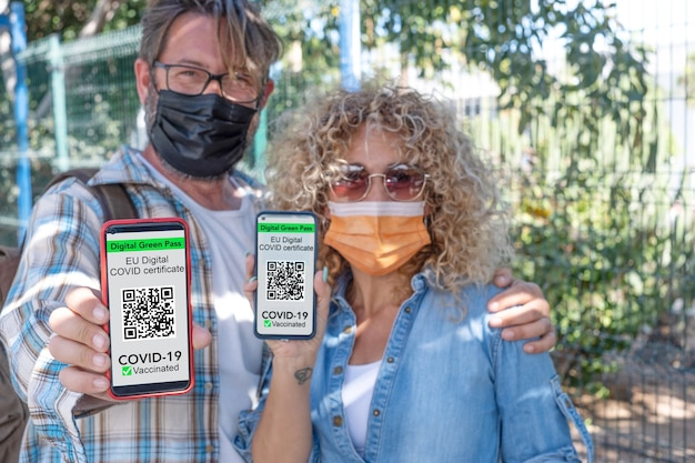 Casal maturo usando máscara cirúrgica segurando um telefone celular com certificado digital de vacinação de covid 19 - foque no telefone