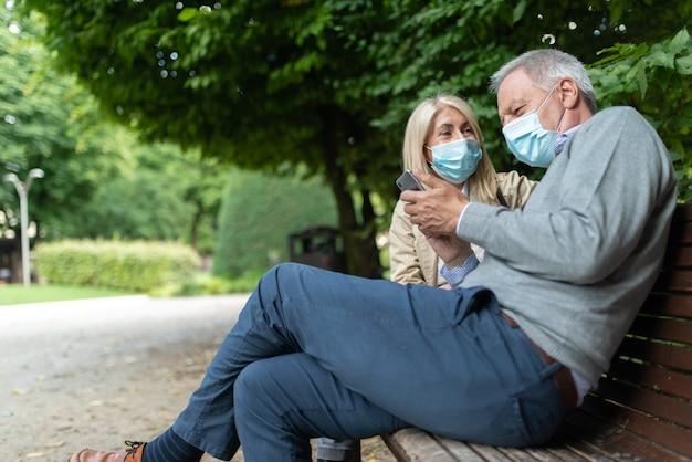 Casal maturo usando telefone celular em um parque durante a pandemia de coronavirus