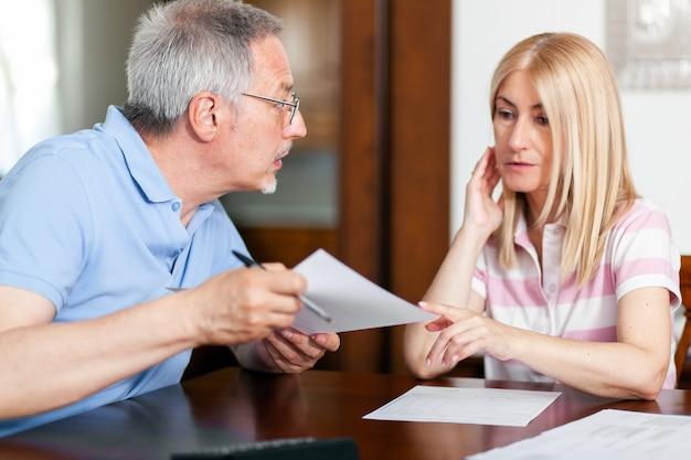 Casal maturo verificando finanças enquanto olha as contas
