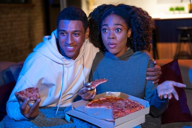 Casal mediano comendo pizza