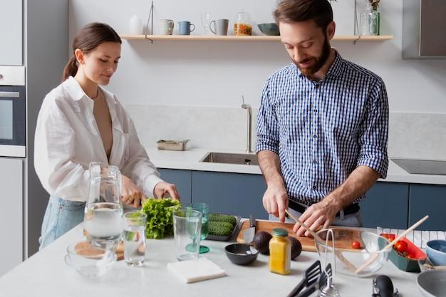 Casal mediano cozinhando em casa