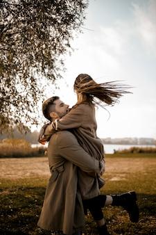 Casal mediano se abraçando ao ar livre