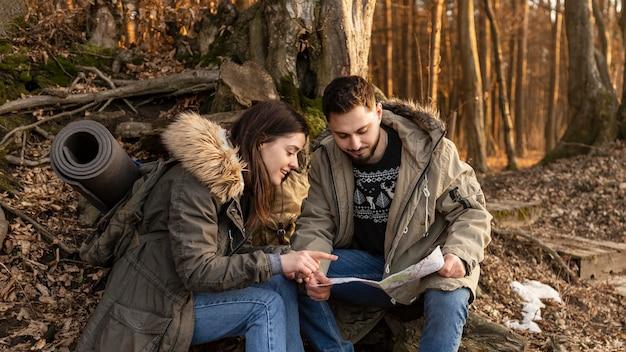 Casal médio com mapa sentado