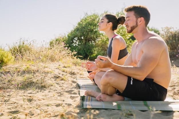 Casal meditando na praia