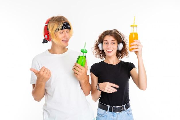 Casal menina e menino em fones de ouvido com copos de vidro com suco em branco