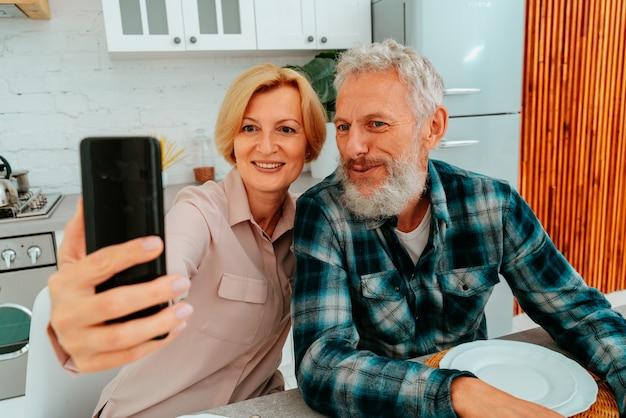 Casal miling tirando uma selfie com um smartphone durante o café da manhã