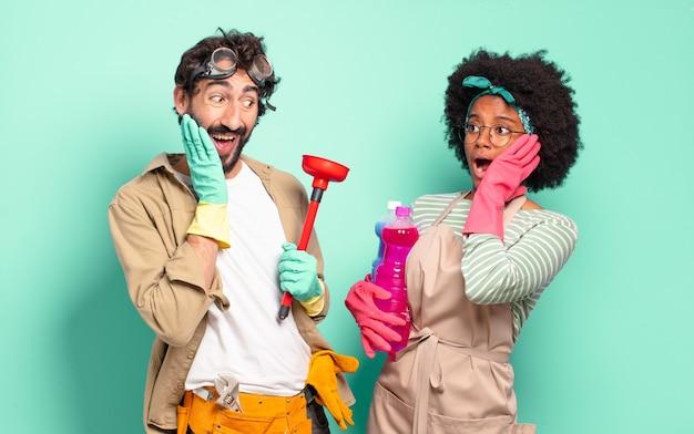 Casal misto se sentindo feliz, animado e surpreso, olhando para o lado com as duas mãos no rosto conceito de limpeza conceito de reparos domésticos