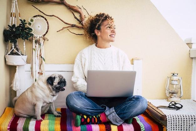 Casal moderno com uma mulher muito encaracolada e um cãozinho engraçado sentado na viga em casa, trabalhando com um laptop