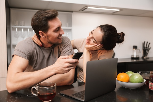 Casal moderno, homem e mulher, usando laptop com smartphone, enquanto está sentado na cozinha
