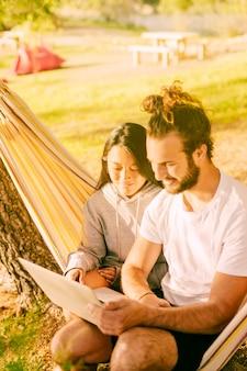Casal moderno relaxante juntos na rede ao ar livre