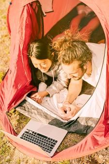 Casal moderno relaxante na tenda com laptop