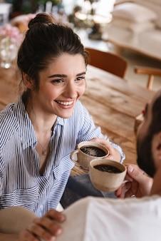 Casal moreno feliz homem e mulher bebendo café juntos enquanto estão sentados à mesa em casa
