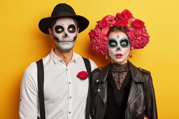 Casal morto-vivo assustador vestido com fantasia de carnaval, usa maquiagem de caveira, flores vermelhas como símbolo deste evento.