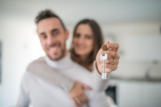 Casal mostrando as chaves da sua nova casa