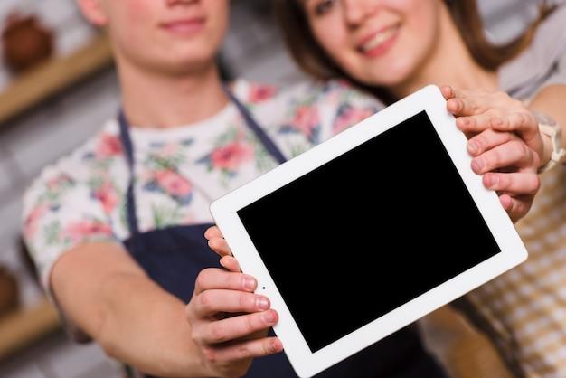 Casal mostrando tablet moderno juntos