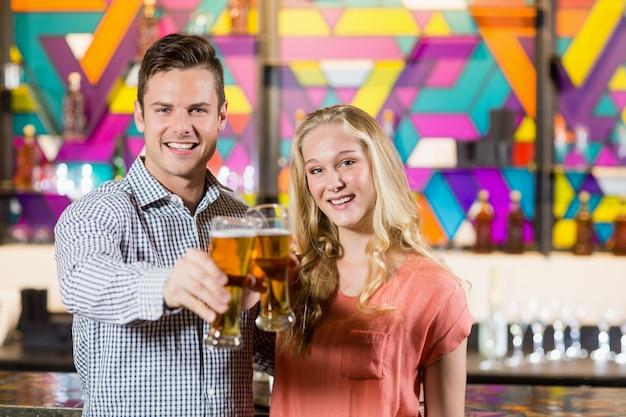 Casal mostrando um copo de cerveja no bar