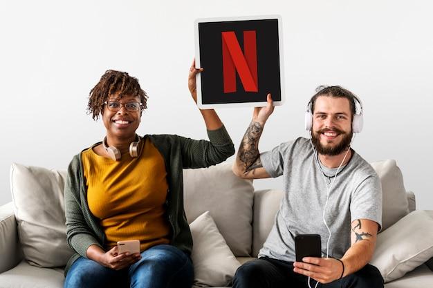 Casal mostrando um ícone da netflix