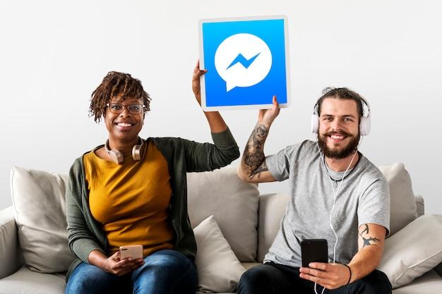 Casal mostrando um ícone do facebook messenger