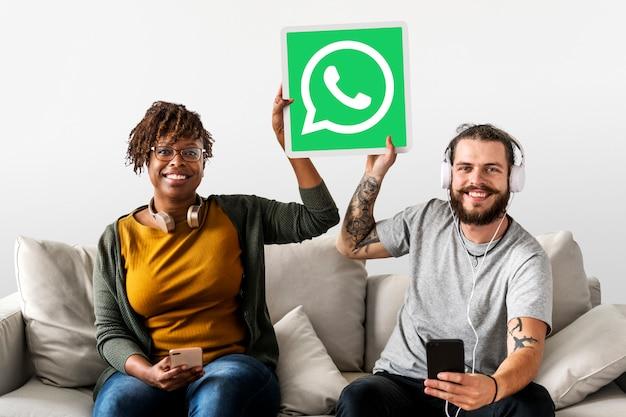 Casal mostrando um ícone do whatsapp messenger