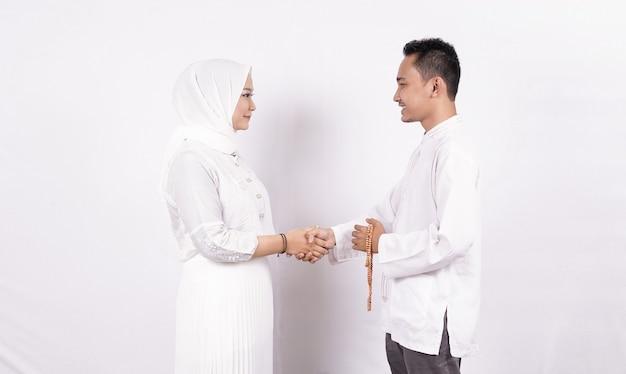 Casal muçulmano asiático cumprimentando um casal em ramadã isolado