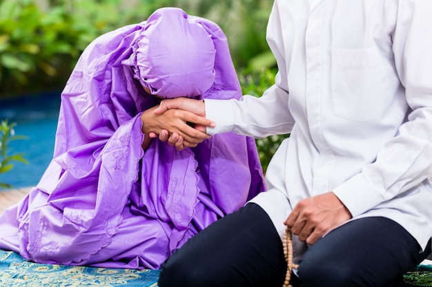 Casal muçulmano asiático, homem e mulher, rezando em casa