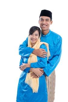 Casal muçulmano asiático segurando a mão isolada sobre o branco