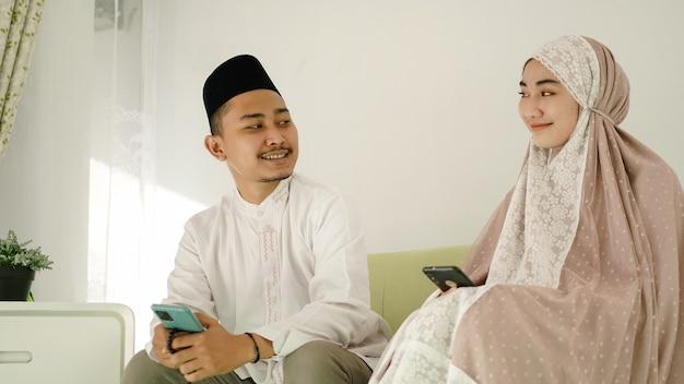 Casal muçulmano asiático sentado relaxando no sofá