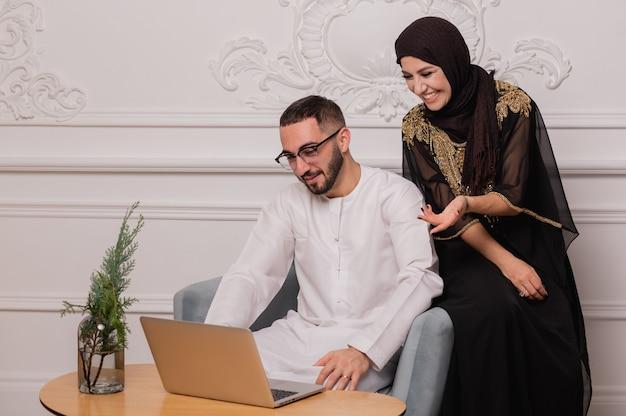 Casal muçulmano com roupas nacionais se comunica por vídeo-comunicação. videoconferência com amigos.