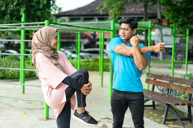 Casal muçulmano conversando em pé fazendo movimentos de aquecimento antes de se exercitar no parque