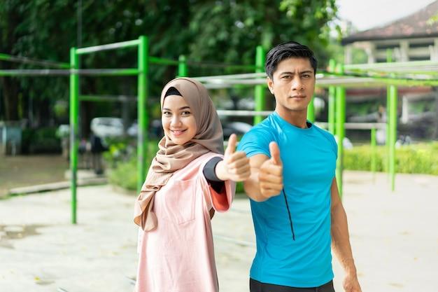Casal muçulmano faz exercícios de costas um para o outro no parque, mostrando o polegar para cima