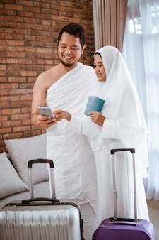 Casal muçulmano fazendo uma ligação enquanto umrah e hajj