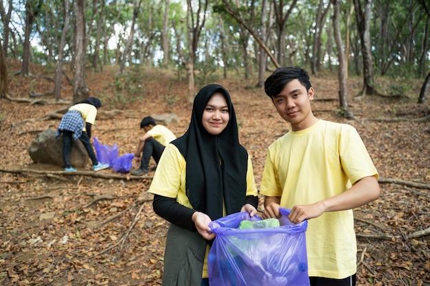 Casal muçulmano sorrindo voluntário segurando o saco de lixo