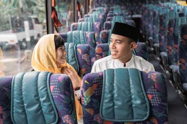 Casal muçulmano viaja de ônibus durante o feriado de eid mubarak para encontrar a família em casa