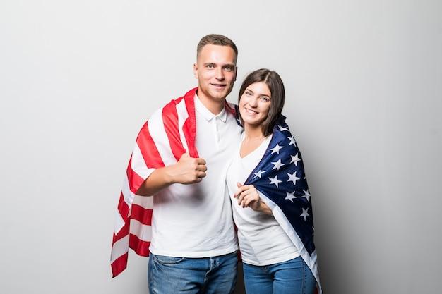 Casal muito sorridente segura a bandeira dos eua nas mãos e se cobre isolado no branco