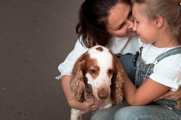 Casal mulher e menina mãe e filha se abraçando com um cachorro em fundo cinza