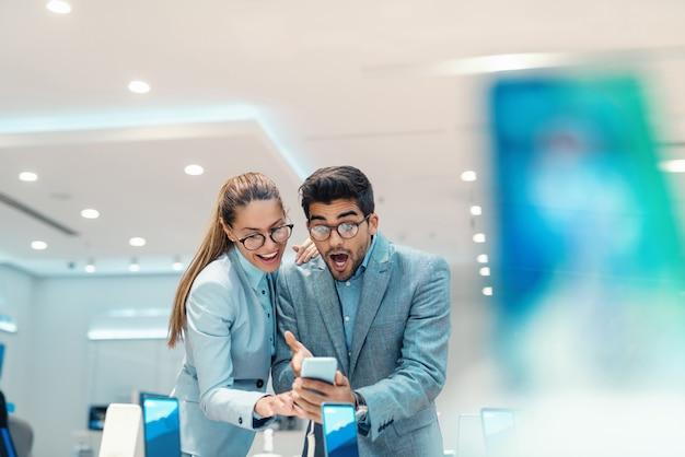 Casal multicultural atraente espantado vestido elegante escolhendo novo telefone inteligente em pé na loja de tecnologia.