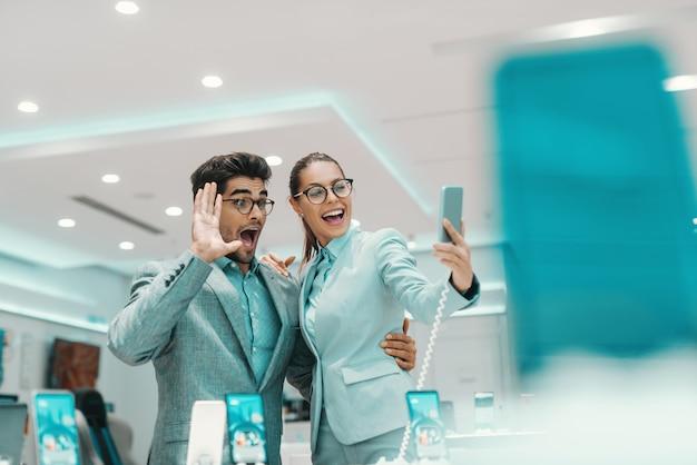 Casal multicultural jovem sofisticado vestido formal tomando selfie com novo telefone inteligente na loja de tecnologia
